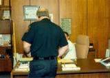 Officer Phil Savage standing in front of Dr. Ohm's desk